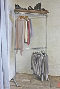Industrial style galvanised steel pipe double clothes rail with reclaimed scaffolding timber shelves above and below