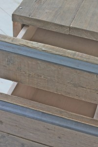 close up of urban bespoke reclaimed scaffolding board drawer unit on castors with angular steel handles