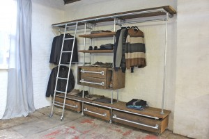 Industrial style wall, and floor, mounted reclaimed scaffolding timber shelves, hanging rails, access rolling ladder and storage drawers