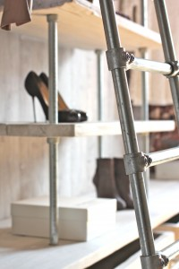 modern industrial style clothes rail with bright orange details and ladder