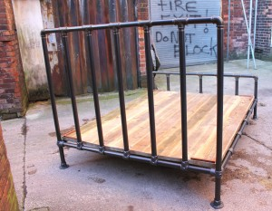 dark steel pipe bed-frame with reclaimed scaffolding board base